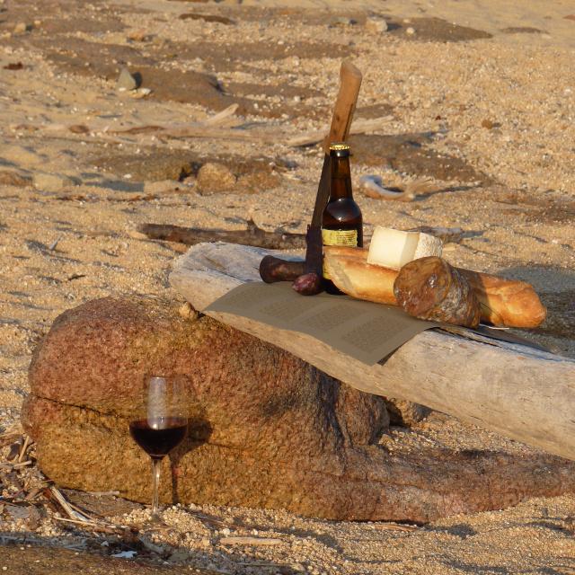 Apéritif sur la plage proche de la villa à louer en corse du sud, au coucher du soleil, charcuterie et fromage corse sur un bois flot.